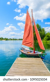 Small traditional sailing boat mooring at wooden pier on Kryspinow lake marina on sunny summer day, Poland