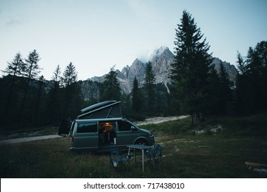 Small travel vehicle camping van or big car with folding rooftop with bed is parked on secluded wild site under huge mountain formation in dolomites, surrounded by forest