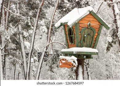 A small tree house in a snowy forest on a clear winter frosty day
