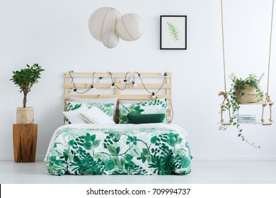 Small tree in pot on wooden designer table next to bed with floral overlay in inspiring bedroom with handmade swing