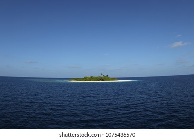 Small tropical island sits in the middle if the vast blue pacific ocean
