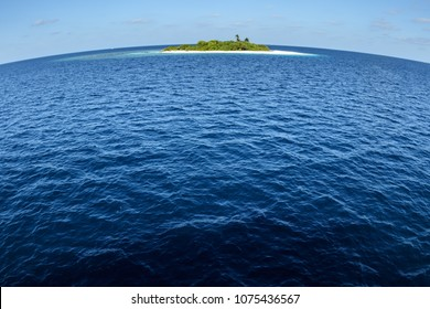 Small tropical island sits in the vast pacific ocean with curved horizon of round earth