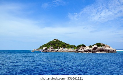 Small tropical rocky island surrounded by the sea. Shot from afar in broad daylight.