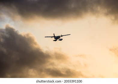 Small turboprop seaplane in the sunset sky.