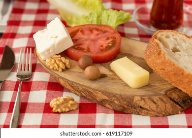 Small Turkish breakfast plate, white cheese, kashkaval cheese, tomato, slice of bread, green olives, lettuce, walnuts and glass of tea on plaid table cloth