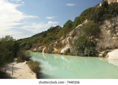 A small turquoise pool filled by a hot thermal spring in Bagno Vignoni, Tuscany