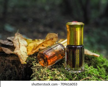 Small unopened bottle with the contents on the green natural background. A small bottle of agarwood oil at natural green background. The Oil Of Oud. Arab Attar.