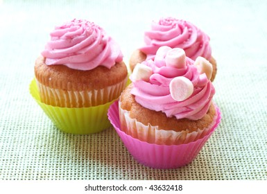 Small vanilla cupcakes with strawberry icing and marshmallows on green mesh background