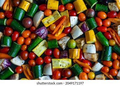 petits légumes de toutes les couleurs coupés et dispersés sur une plaque de cuisson