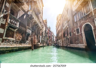 Small venetian canal and old brick walls with vintage traditional balconies. Venice, Italy.