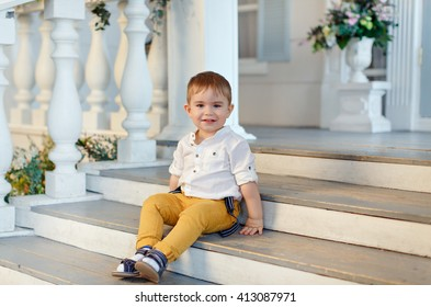 Small very cute, charming boy in yellow trousers sits on the stairs and laughing, against the background of home interior