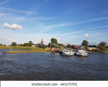 small village alongside the Waal River and inland shipping boats, Waal River Netherlands June 2017