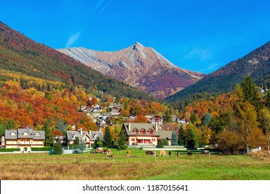 Small village among colorful autumnal hills and mountains under blue sky in Switzerland.