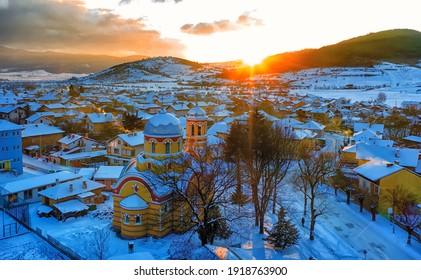 Kleines Dorf in Bulgarien Drohnenbild. Sonnenuntergang. Orthodoxe Kirche im Vordergrund.