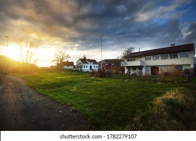 Small village in fjords at sunset. Hidra island, Rogaland region, Norway. Traditional architecture. Dramatic evening sky. Travel destinations theme