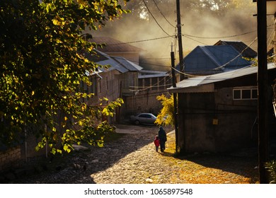 a small village at the foot of the mountains, a paved street in the rays of the morning sun