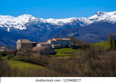Small village with forest and snowy mountains in background in the french Pyrenees, Ariege