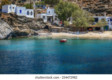 Small village of Mali, in Tinos island, Greece, with clear transparent waters and a fishing boat