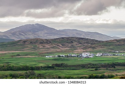 A small village on the island of Jura sits beneath large hills and is surrounded by farmland. Viewed from the island of Islay, Scotland.