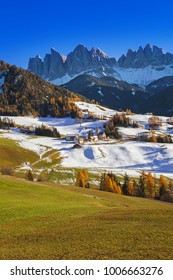 The small village of St. Magdalena or Santa Maddalena with its church covered in snow and with the Odle or Geisler Dolomites mountains in the Val di Funes Valley, South Tyrol, Italy in winter.