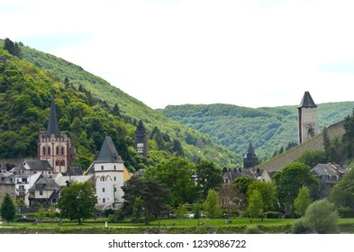 A small village of traditional houses by a river in Germany. Castle, church and granary towers rise above the buildings. The surrounding hills are covered with forest, with a vineyard On one slope.