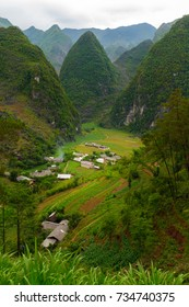 A small village in a valley surrounded by the limestone and granite mountains of Ha Giang, Vietnam.