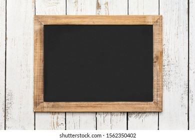 Small vintage blank chalkboard on an old wooden background