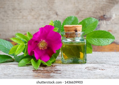 Small vintage bottle with natural rose hip seed oil. Aromatherapy and natural skin care concept. Old wooden background with wild rose flower and leaves. Copy space.
