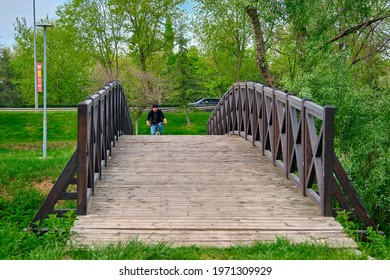 Small vintage bridge inside green grass. Bridge made of wooden material and single man bicycle rider climbing to bridge and there is a car background of the photo in highway Bursa, Turkey. 29.4.2021.