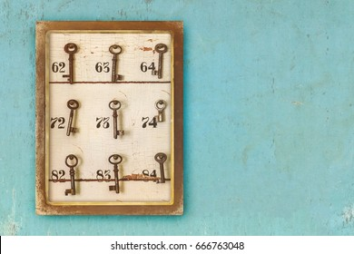 Small vintage cabinet with rusted hotel keys and room numbers on a blue eroded background