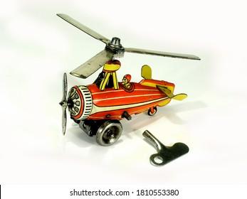 A small vintage Einfalt litho printed clockwork tinplate toy autogyro on white background.