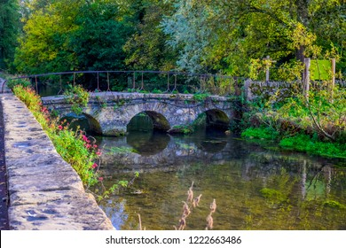 A small vintage stone bridge over river Coln that leads to Arlington Row of Bibury village in Cotswold district, Gloucestershire, England, UK