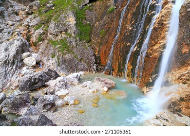 Small water fall collected into blue pond on Lasties valley, Sella massif, Dolomite Alps, Italy