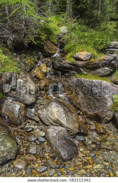 Small waterfall along a mountain path in the Monte Rosa Massif (Ayas Valley, Italy).