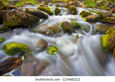 A small waterfall among the large hemmed wet stones covered with moss and green grass. The rapid flow of river blured with long exposure time. English Pond, Peterhof, Saint Petersburg, Russia.