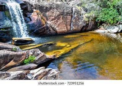 Small waterfall with a beautiful natural pool near a small village in Brazil.
