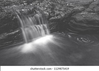 A small waterfall in black and white.