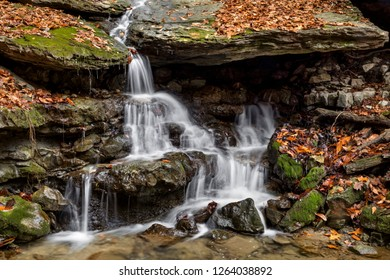 A small waterfall cascades down mossy rocks with autumn leaves all around. Shot at Oglebay Park, Wheeling, West Virginia.