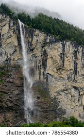 A small waterfall coming down a hill in portrait format.