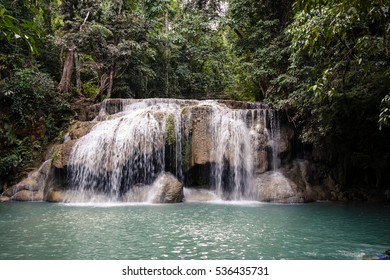 Small waterfall in deep green forest scenery.
