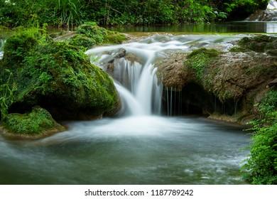 Small waterfall flowing on rock in woodsin long exposure