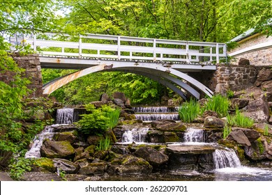 Small waterfall with a footbridge over the falls.