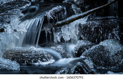 Small waterfall in a forest creek with frozen rocks and icicles