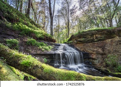 Small waterfall in the forest. Narrow creek in gorge ending in cascading water. Fallen trees covered with bright green moss. Typical limestone escarpment. Water flow through Nordic jungle. Estonia.