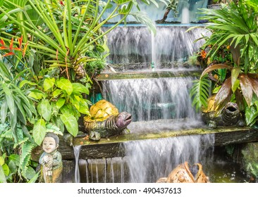 Small waterfall in garden pond.