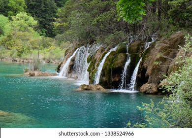small waterfall in Jiuzhaigou Valley Sichuan China. pure clean water falling into green lake. forest jungle around