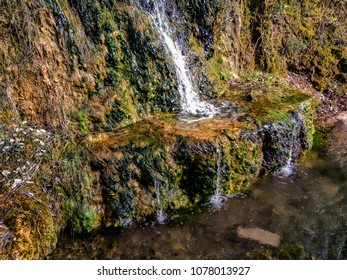 Small waterfall with moss under sunny day
