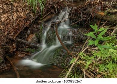 Small waterfall near Kouty nad Desnou village in summer day in forest - Shutterstock ID 1800928267
