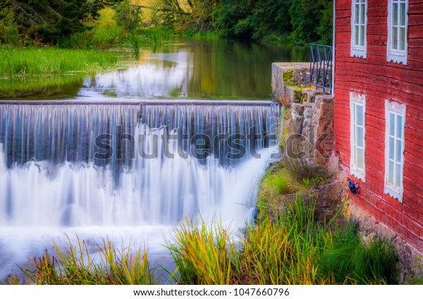 Small waterfall next to red building. This place can be seen in a small place called Resville in southwestern part of Sweden 08/30/16