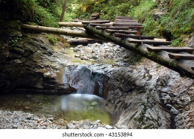 A small waterfall on a forest stream with boardwalk in Slovakian paradise.